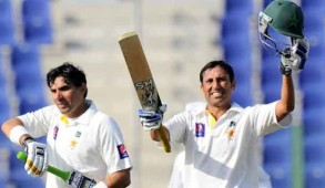 Pakistan batsman Younis Khan (R) celebrates after scoring a century (100 runs) as teammate, batsman Misbah-ul-Haq (L), looks on during the second day of the first cricket Test match between Pakistan and Sri Lanka at the Sheikh Zayed Stadium in Abu Dhabi on January 1, 2014. Sri Lanka were bowled out for 204 in their first innings of the first Test against Pakistan in Abu Dhabi. AFP PHOTO/Ishara S. KODIKARA